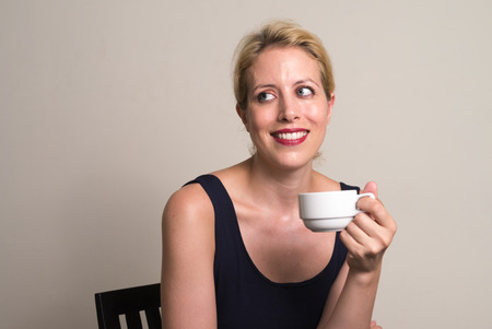 only mid adult women: Portrait of woman holding coffee cup