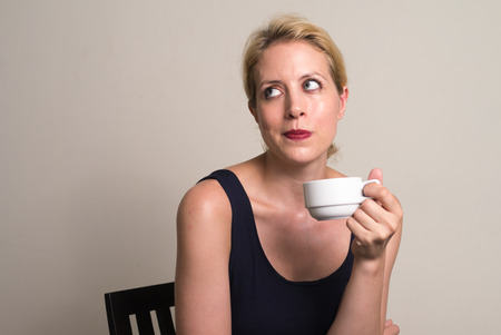 one mid adult woman only: Portrait of woman holding coffee cup