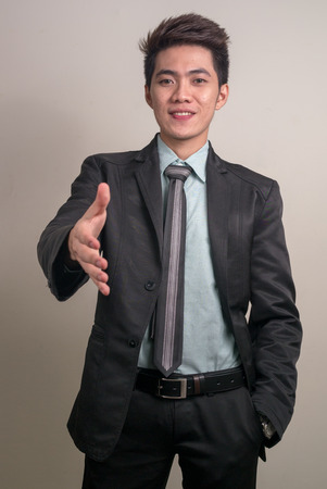 filipino adult: Asian young businessman offering his hand