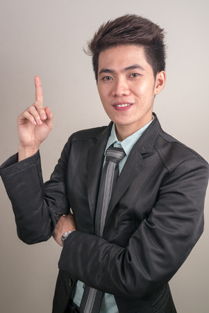filipino ethnicity: Portrait of Asian young businessman pointing to copy space