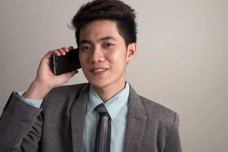 filipino ethnicity: Asian young businessman using phone