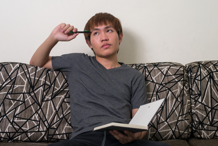 one person only: Young Asian man sitting on sofa