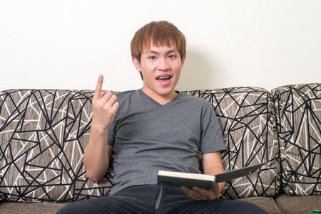 one person only: Asian young man sitting on sofa