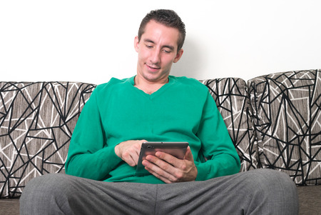 only one mid adult male: Man sitting and using digital tablet