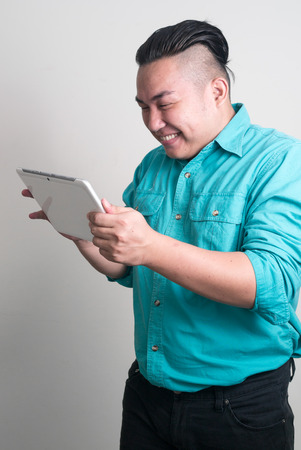 filipino ethnicity: Overweight Asian man using digital tablet Stock Photo
