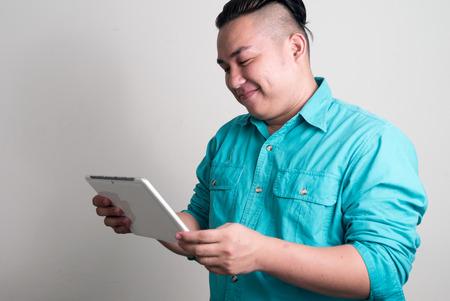 filipino ethnicity: Overweight Asian man using digital tablet Stock Photo