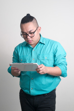 only one mid adult male: Overweight Asian man using digital tablet Stock Photo
