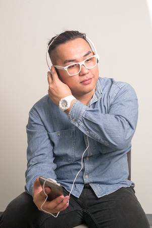 filipino ethnicity: Overweight man listening music with headphones Stock Photo