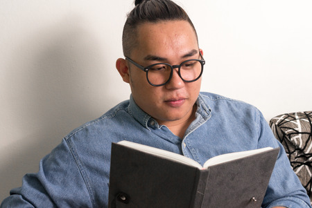 only one mid adult male: Overweight Asian man reading book