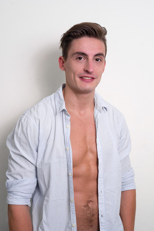 partially nude: Handsome man standing with shirt open