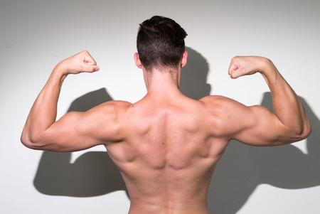partially nude: Bodybuilder posing and showing his muscular back