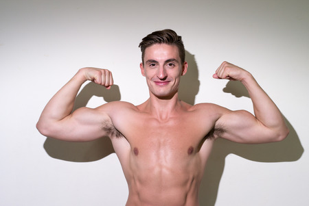 partially nude: Man flexing his biceps and smiling