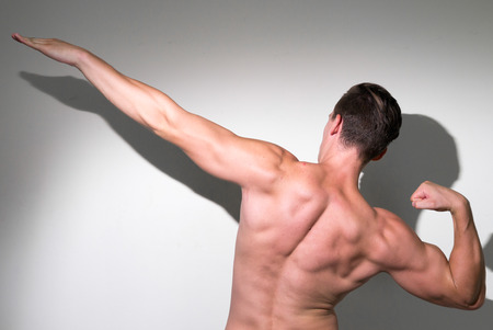 partially nude: Bodybuilder posing and showing his muscular body