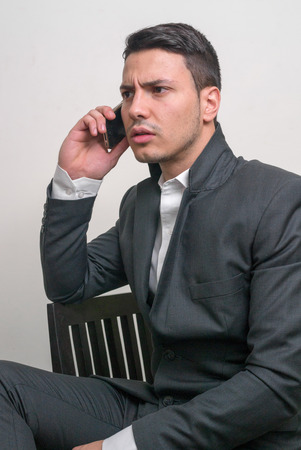 telephoning: Young businessman using cell phone vertical studio shot Stock Photo
