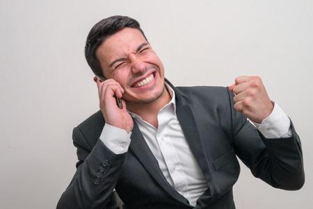 telephoning: Young businessman using cell phone horizontal studio shot Stock Photo