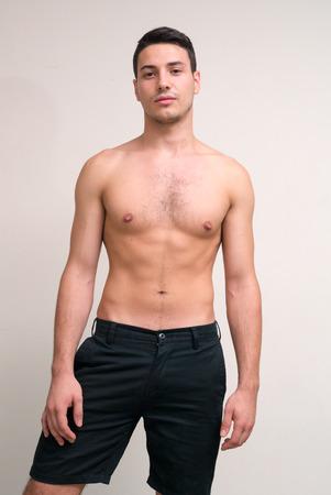 partially nude: Sexy shirtless man vertical studio shot