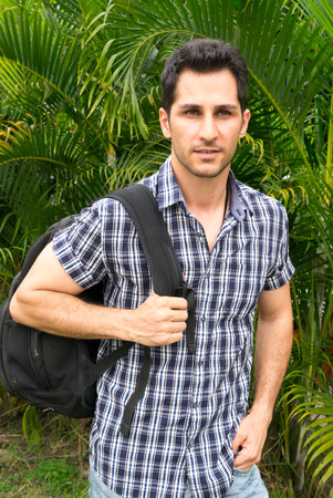 tourist guide: Middle Eastern handsome tourist guide with backpack outdoors