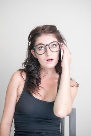 telephoning: Sexy woman talking on phone vertical studio shot