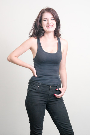 sexy woman standing: Sexy woman standing and smiling vertical studio shot
