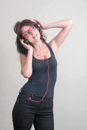 sexy headphones: Sexy woman wearing red glasses and listening music with headphones vertical studio shot Stock Photo