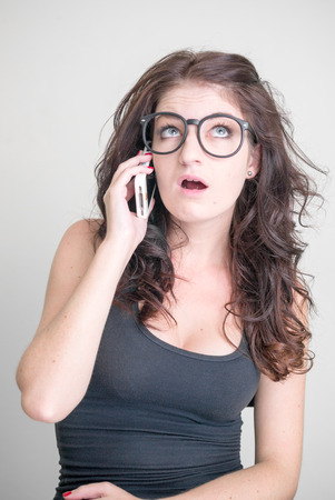 telephoning: Sexy woman wearing black glasses and using cellular phone vertical studio shot