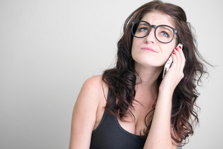 sexy woman on phone: Sexy woman wearing black glasses and using cellular phone horizontal studio shot