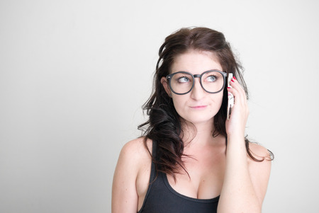 sexy woman: Sexy woman wearing black glasses and using cellular phone horizontal studio shot