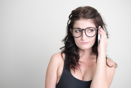 donna sexy: Donna sexy che porta gli occhiali neri e utilizzando telefono cellulare in studio tiro orizzontale