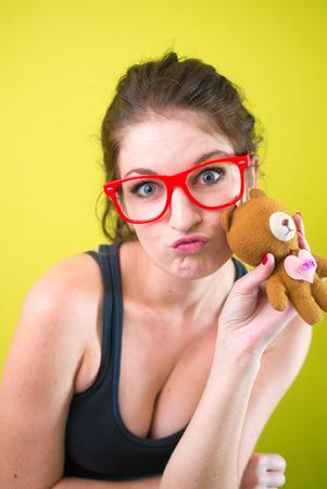 donna sexy: Donna sexy che porta gli occhiali rossi che tengono il giocattolo in mano