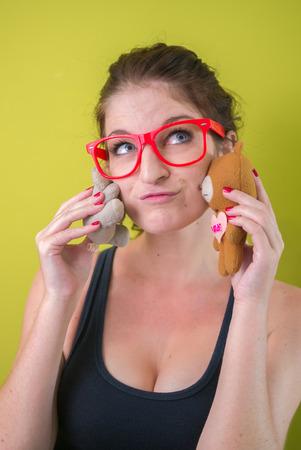mujer sexy: Mujer atractiva con gafas de color rojo y la celebraci�n de juguetes en sus manos
