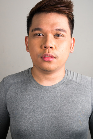 only one mid adult male: Portrait of young Filipino man vertical studio shot