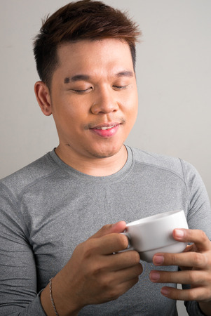 filipino ethnicity: Portrait of young Filipino man holding cup of coffee  vertical studio shot