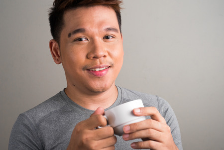 filipino ethnicity: Portrait of young Filipino man holding cup of coffee horizontal studio shot