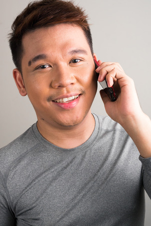 filipino ethnicity: Portrait of young Filipino man using cellular phone vertical studio shot