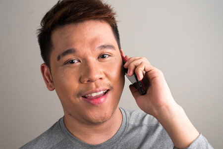telephoning: Portrait of young Filipino man using cellular phone horizontal studio shot