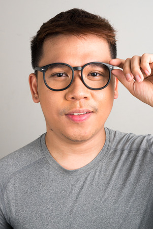 one mid adult man only: Portrait of young Filipino man wearing black eyewear vertical studio shot