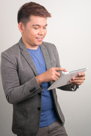 filipino ethnicity: Young Filipino man using digital tablet vertical studio shot Stock Photo