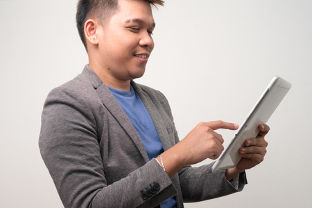 only one mid adult male: Young Filipino man using digital tablet Stock Photo