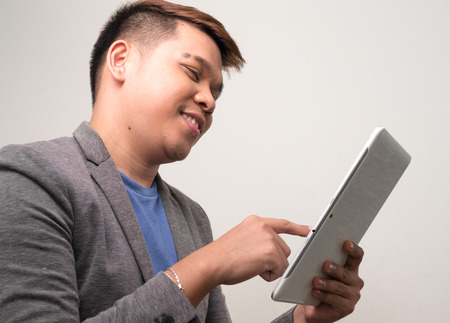 filipino ethnicity: Young Filipino man using digital tablet Stock Photo