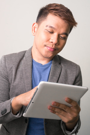 one mid adult man only: Young Filipino man using digital tablet Stock Photo