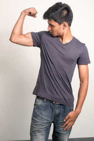 only the biceps: Portrait of a handsome young Indian man flexing his bicep Stock Photo