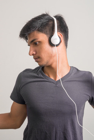head phones: Portrait of a handsome young Indian man listening music with head phones