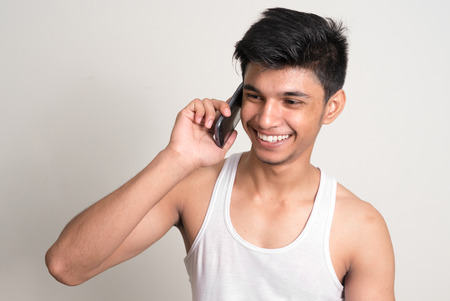 telephoning: Portrait of a handsome young Indian man using smart phone