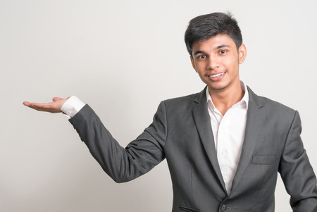endorsing: Portrait of a handsome young smiling Indian man holding his hand open presenting copyspace Stock Photo