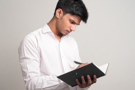 man holding book: Young man holding book and writing