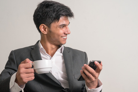 telephoning: Young business man holding cup of coffee and phone while smiling