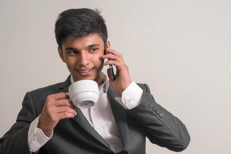 telephoning: Young business man holding cup of coffee and talking on the phone