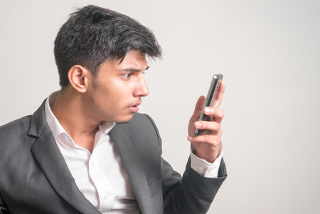 telephoning: Young business man looking to his phone