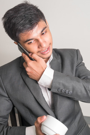 telephoning: Young business man talking on phone and holding coffee cup Stock Photo