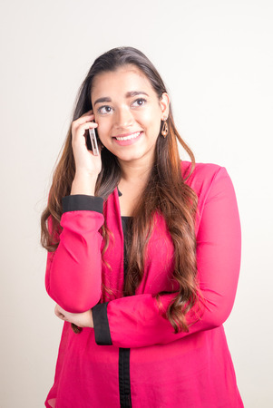 telephoning: Beautiful Indian woman talking on phone vertical studio shot Stock Photo